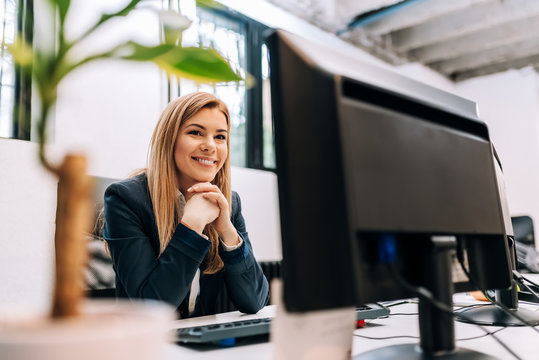 Sucessful smiling businesswoman sitting at the office in front of a computer.