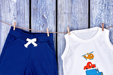 Infant boy summer clothes hanging on rope. Baby boy cute shorts and t-shirt drying on clothesline on old wooden background.