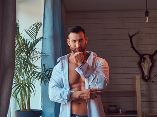 Portrait of a tall bearded male with a muscular body.