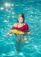 Woman relax in spa pool. Summer vacation and travel to ocean. Vitamin in banana at girl sitting near water. Dieting and healthy organic food, vegetarian. woman with tropical fruit in pool.