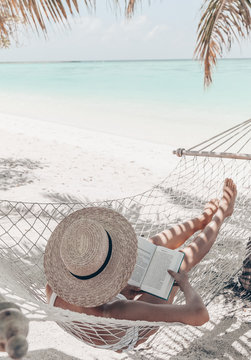 Maldive islands. girl is relaxing in hammock and reading book