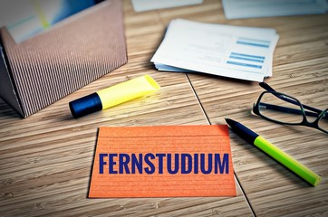 Index cards with legal issues with glasses, pen and bamboo with the german word Fernstudium in english Distance law