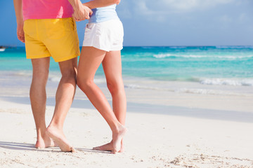 legs of young hugging couple in love on tropical turquoise beach