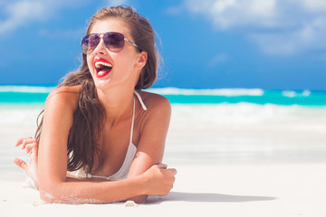 portrait of long haired girl in bikini and wearing red lips on tropical barbados beach