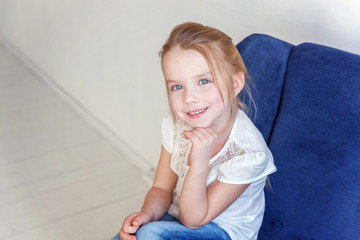 Sweet little girl in jeans and white T-shirt at home sitting on modern cozy blue chair relaxing in white living room