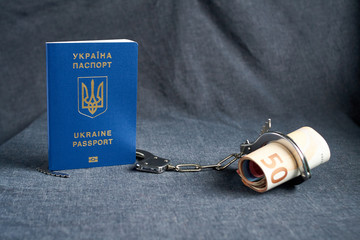 Ukrainian biometric passport and handcuffs on the table.