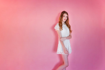 Happy teenage girl smiling. Closeup portrait young happy positive woman wearing white dress standing on pink colourful pastel trendy modern fashion pin-up background. European woman. Positive human