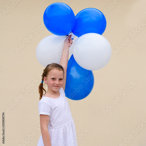 03efc1486 Happy little girl wears white dress holding blue and white balloons ...