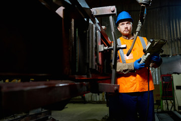 Full length portrait of confident bearded technician wearing reflective vest and hardhat adjusting equipment while standing at production department of modern plant