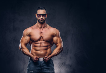 Portrait of a shirtless tall huge male with a muscular body with a stylish haircut and beard, in a sunglasses and jeans, posing in a studio.