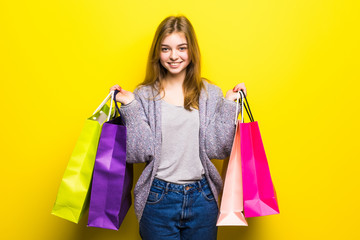 Portrait of young happy smiling teen girl with shopping bags, isolated over yellow background