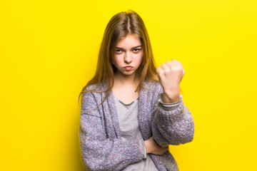 Beautiful sad young teen girl close-up threatens fist into camera, isolated on yellow background.