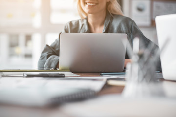 Focus on laptop on table. Smiling blonde woman sitting on background. Low angle