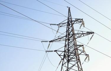 High-voltage tower, transmission line in sky background.