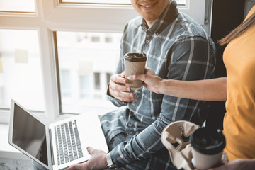 Woman extending hand with drink to male colleague. Man sitting with laptop and taking cup