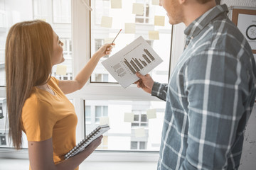 Satisfied man and woman observing paper with graphs while standing at the window