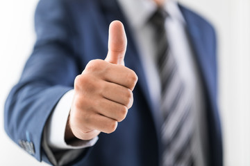 Business man shows thumb up sign gesture.