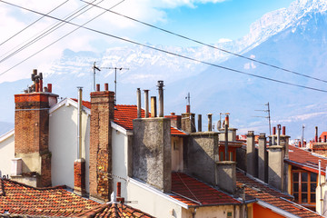 Typical French tiled roofs and chimney pipes in the background of the Alps mountains, Grenoble, France