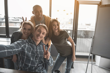 Portrait of four happy people making snapshot of themselves at work. They are showing peace sign taking selfie in office