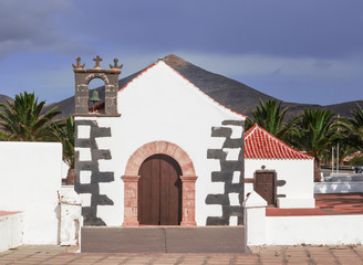small white church with lava stone bell tower at Canary Islands.Fuerteventura