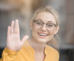 Hi. Portrait of cheerful young woman greeting someone inside glass and laughing