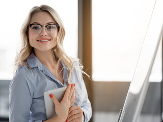 Waist up portrait of smart businesswoman keeping tablet and smiling. She is standing near presentation board and looking at camera with confidence