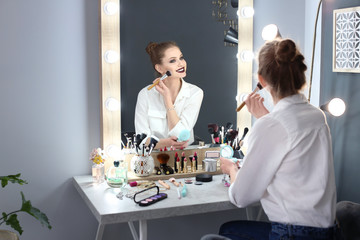 Beautiful young woman applying makeup in dressing room