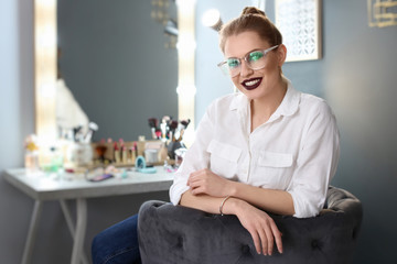 Beautiful young woman with makeup made by professional artist in dressing room