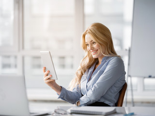 Portrait of glad young businesswoman watching tablet with joy and smiling. Relaxation in office concept