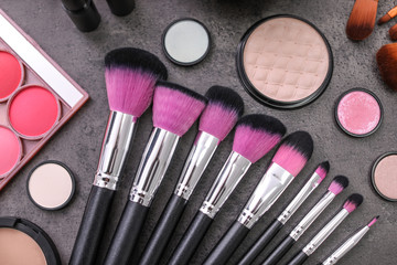 Makeup products and brushes on grey background