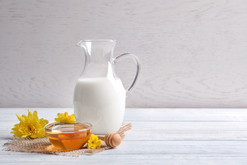 Beautiful composition with milk and honey on wooden table