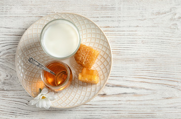 Beautiful composition with milk and honey on wooden background, top view