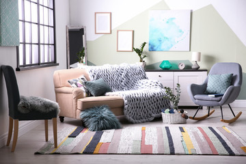 Stylish living room interior with comfortable sofa and rocking chair Wall mural