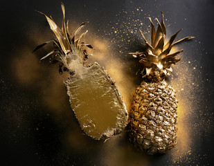 Golden pineapple halves on dark grey background, top view
