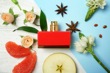 Beautiful composition with bottle of perfume, flowers and fruits on color background, flat lay
