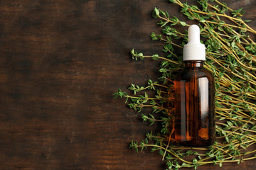 Bottle with thyme essential oil and fresh herb on wooden background