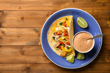 Plate with tasty creamy sauce in bowl and fish taco on wooden table
