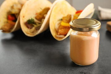 Tasty creamy sauce for fish taco in glass jar on kitchen table