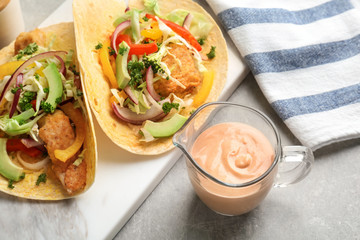 Tasty creamy sauce in jug and fish tacos on kitchen table