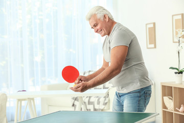 Senior man playing table tennis indoors