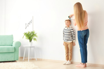 Young woman measuring height of little boy at home