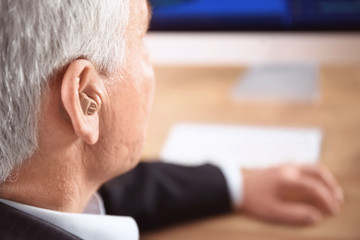 Mature man with hearing aid indoors