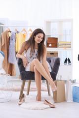 Young beautiful woman choosing shoes while shopping in store