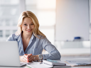 Waist up portrait of polite office worker listening to client attentively. She is looking forward and smiling. Woman is sitting at desk near laptop. Copy space