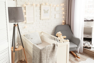 Interior of light modern children's room with crib