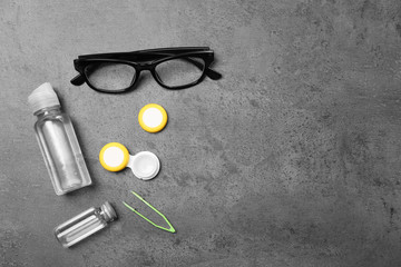 Glasses and contact lens accessories on grey background, top view