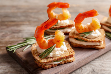 Delicious small sandwiches with shrimps on wooden board