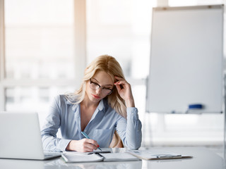 Portrait of pensive blond businesswoman writing thoughts in notebook. She is sitting at table in office
