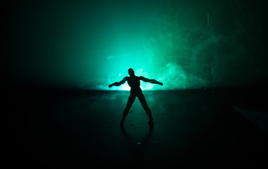 Silhouette of man standing on an dark foggy toned background. Decorated photo with man figure on table with light.
