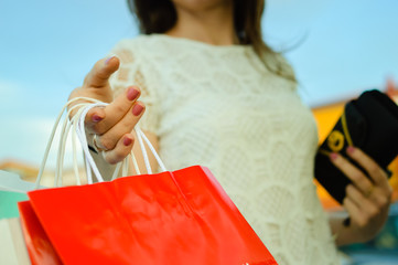 Close up on hand of a woman hold paper bag doing shopping over busy lifestyle background. Modern consumerism, buying, spending trend and marketing solution